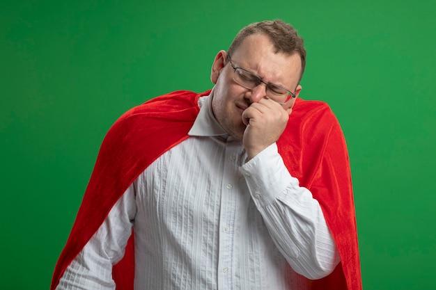 Schmerzhafter erwachsener superheldenmann im roten umhang, der eine brille trägt, die hand auf die wange setzt, die unter zahnschmerzen mit geschlossenen augen leidet, die auf grüner wand lokalisiert werden