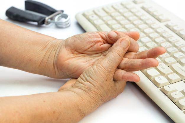 Schmerzhafter finger der älteren frau aufgrund längerer verwendung von tastatur und maus.