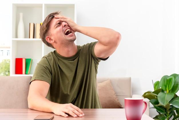 Schmerzhafter junger blonder gutaussehender mann sitzt am tisch mit telefon und tasse, die hand auf gesicht im wohnzimmer setzen