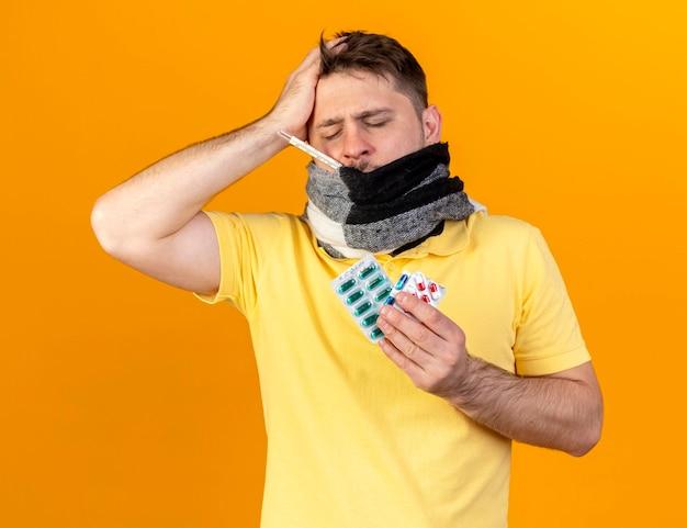 Schmerzhafter junger blonder kranker slawischer mann, der mund mit schal bedeckt