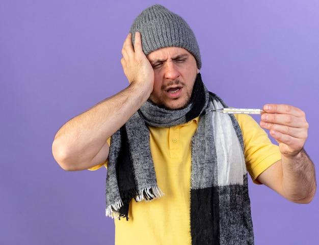 Schmerzhafter junger blonder kranker slawischer mann, der wintermütze trägt