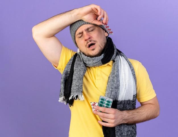 Schmerzhafter junger blonder kranker slawischer mann, der wintermütze und schal trägt