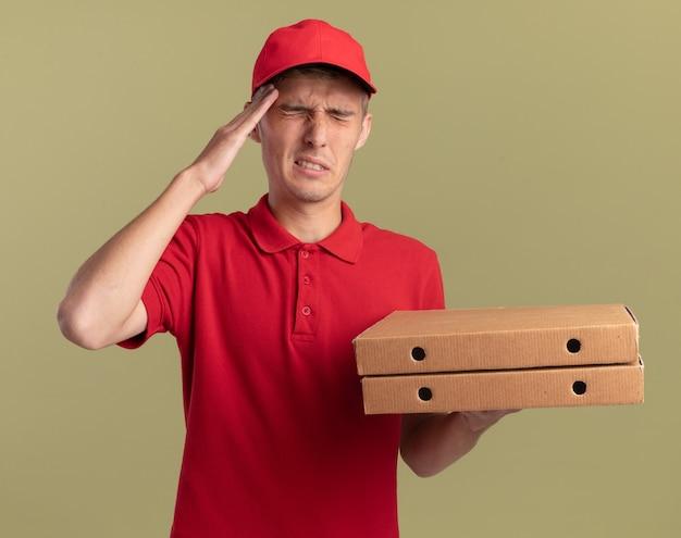 Schmerzhafter junger blonder lieferjunge legt hand auf stirn und hält pizzaschachteln isoliert auf olivgrüner wand mit kopienraum
