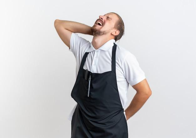Schmerzhafter junger gutaussehender friseur in uniform, der seinen nacken und rücken mit geschlossenen augen hält, die unter schmerzen leiden, die auf weiß mit kopienraum isoliert sind