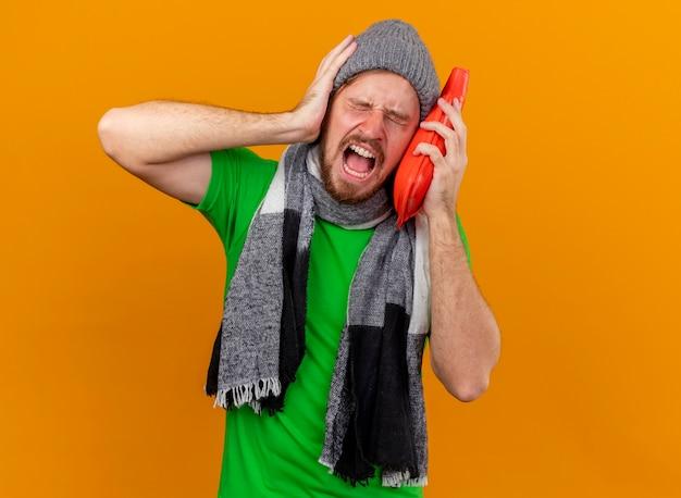 Schmerzhafter junger gutaussehender slawischer kranker mann, der wintermütze und schal hält, die heißes wasserbeutel-berührendes gesicht mit ihm halten hand auf kopf halten, der kopfschmerzen lokalisiert auf orange wand mit kopienraum hält