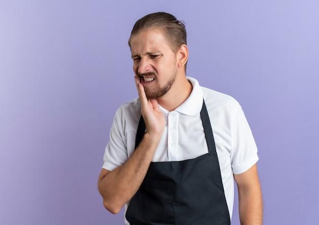 Schmerzhafter junger hübscher friseur, der uniform trägt, die hand auf die wange legt, die unter zahnschmerzen leidet, die auf purpur mit kopienraum isoliert werden