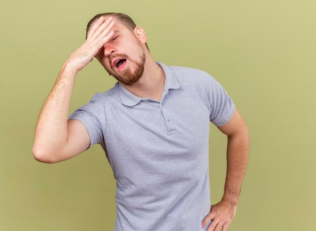 Schmerzhafter junger hübscher kranker mann, der hand auf taille und einen anderen auf kopf mit geschlossenen augen hält, die auf olivgrüner wand isoliert werden