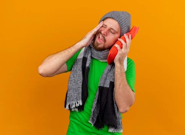 Schmerzhafter junger hübscher slawischer kranker mann, der wintermütze und schal hält, die heißes wasserbeutel-berührungsgesicht mit ihm mit geschlossenen augen halten, die auf orange wand mit kopienraum isoliert sind