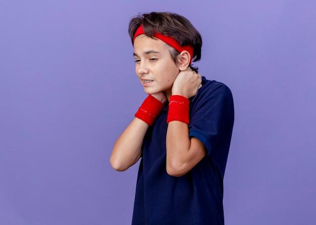 Schmerzhafter junger hübscher sportlicher junge, der stirnband und armbänder mit zahnspangen trägt, die gerade halten hände hinter dem hals lokalisiert auf lila wand suchen