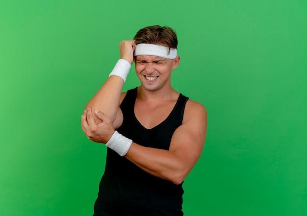 Schmerzhafter junger hübscher sportlicher mann, der stirnband und armbänder trägt, die hand auf kopf und einen anderen auf ellbogen setzen, der unter schmerzen leidet, die auf grün mit kopierraum isoliert werden