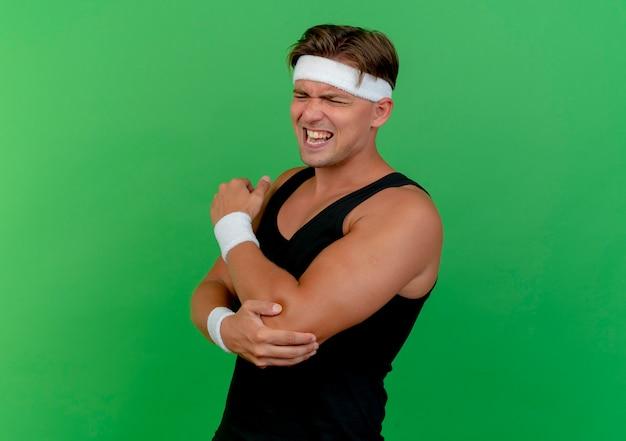 Schmerzhafter junger hübscher sportlicher mann, der stirnband und armbänder trägt, die hand auf seinen ellbogen setzen, der unter schmerzen mit geschlossenen augen leidet, die auf grün mit kopienraum isoliert werden