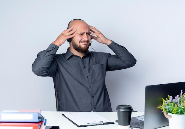 Schmerzhafter junger kahlköpfiger callcenter-mann, der headset trägt, das am schreibtisch mit arbeitswerkzeugen sitzt, die seite betrachten hände auf kopf lokalisiert auf weiß setzen