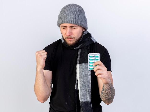 Schmerzhafter junger kaukasischer kranker mann, der wintermütze und schal trägt, hält faust und hält packung der medizinischen kapseln auf weiß