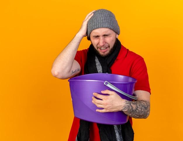 Schmerzhafter junger kaukasischer kranker mann, der wintermütze und schal trägt, legt hand auf kopf, der plastikeimer hält, der übelkeit lokalisiert auf orange wand mit kopienraum hält