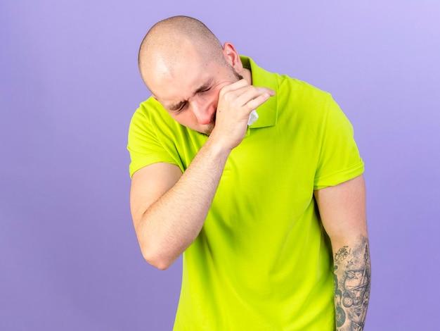 Schmerzhafter junger kaukasischer kranker mann legt hand auf gesicht, das gewebe auf purpur hält