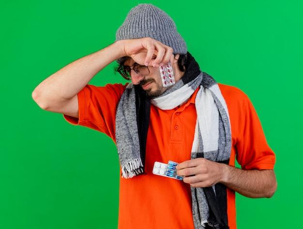 Schmerzhafter junger kranker mann, der brille wintermütze und schal hält, die medizinische pillen berühren kopf lokalisiert auf grüner wand halten