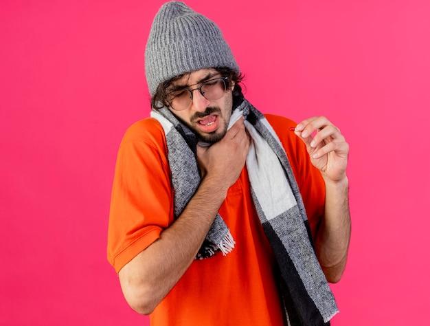 Schmerzhafter junger kranker mann, der brille wintermütze und schal hält hals hält hand in luft mit geschlossenen augen lokalisiert auf rosa wand mit kopienraum