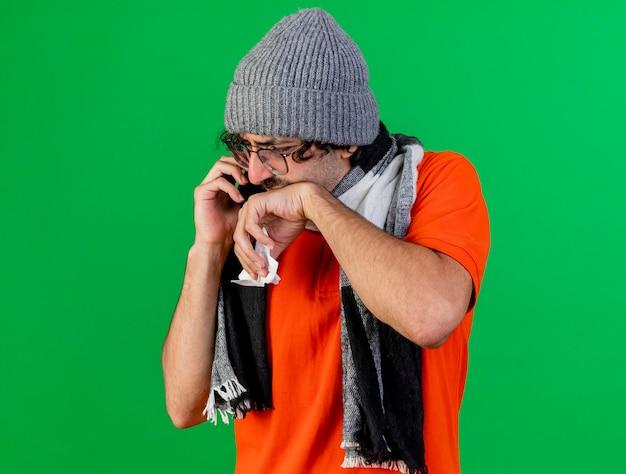 Schmerzhafter junger kranker mann, der brille wintermütze und schal trägt, die am telefon sprechen serviette halten hand auf mund halten, der unten auf grüner wand mit kopienraum schaut