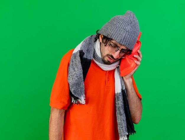 Schmerzhafter junger kranker mann, der brillenwintermütze und -schal trägt, die heißen wasserbeutel auf kopf mit geschlossenen augen setzen, lokalisiert auf grüner wand mit kopienraum