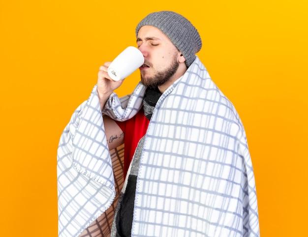 Schmerzhafter junger kranker mann, der wintermütze und schal trägt, die in die tasse tee des plaidgetränks eingewickelt werden, lokalisiert auf orange wand
