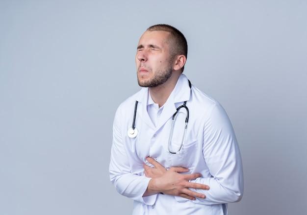 Schmerzhafter junger männlicher arzt, der medizinische robe und stethoskop um seinen hals trägt und seinen bauch hält, der unter schmerzen mit geschlossenen augen leidet, die auf weiß mit kopierraum isoliert werden