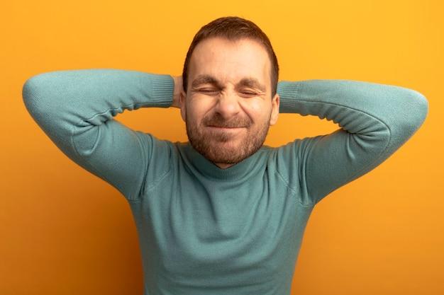 Schmerzhafter junger mann, der hände hinter kopf mit geschlossenen augen setzt, die auf orange wand isoliert werden Kostenlose Fotos