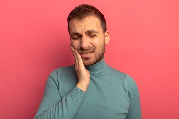 Schmerzhafter junger mann, der hand auf wange legt, die unter kopfschmerzen mit geschlossenen augen leidet, die auf rosa wand isoliert werden