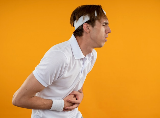 Schmerzhafter junger sportlicher kerl, der stirnband mit armband trägt, packte bauch isoliert auf gelber wand