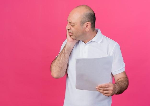 Schmerzhafter lässiger reifer geschäftsmann, der dokumente hält, die hand auf wange leiden, die unter zahnschmerzen leidet, lokalisiert auf rosa hintergrund mit kopienraum