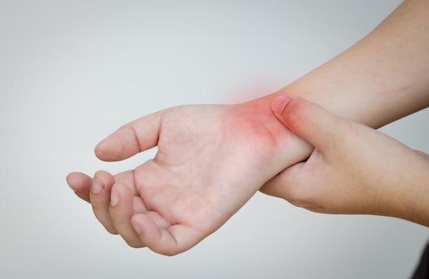 Schmerzhandgelenk mit einer anderen hand, die als schmerzbereich drückt