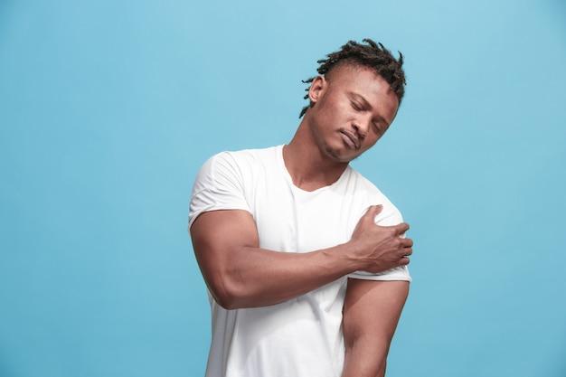 Schmerzkonzept. schönes afro männliches porträt lokalisiert auf blauem hintergrund. junger emotional überraschter mann, der kamera betrachtet. menschliche emotionen, gesichtsausdruckkonzept. mann mit schmerzen in der schulter überwältigt