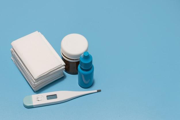 Schmerzmittel taschentücher tropfen und thermometer blauer hintergrund