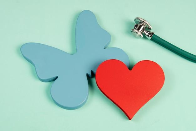 Schmetterling, der die schilddrüse und die form eines herzens symbolisiert, die sich auf die behandlung von problemen im zusammenhang mit den 2 organen beziehen Premium Fotos