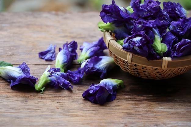 Schmetterlingserbse blüht blaue farbe in den asiatischen kräuterblumen des korbes auf hölzernem hintergrund