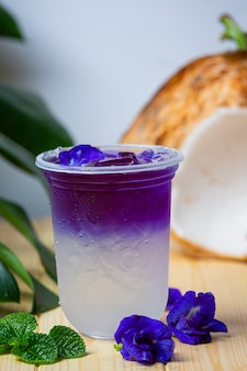 Schmetterlingserbsensaft mit kokosnuss auf holzoberfläche