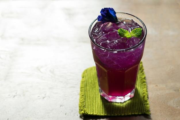 Schmetterlingserbsensaft mit zitrone im kalten glas, thailändisches krautgetränk für gesundheit.