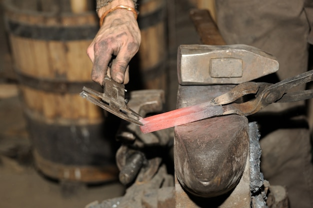 Schmied, der in der schmiede arbeitet, verarbeitet das metall. das foto zum thema schmiedekunst