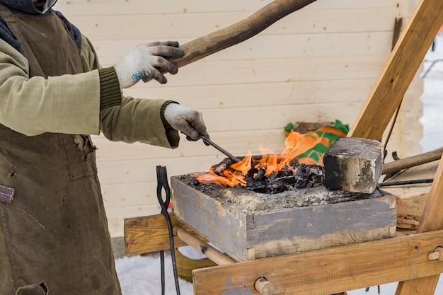 Schmied, der manuell das flüssige metall auf dem amboss draußen schmiedet