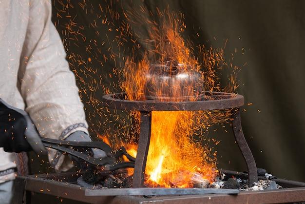 Schmied, der metall in glühenden kohlen aufheizt, während teekanne wasser oben kocht.