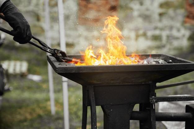 Schmied, der metallstück in brennender kohle erhitzt