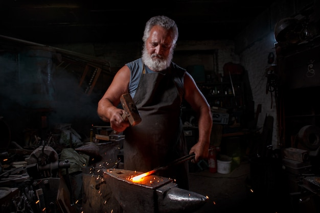 Schmied handwerker in schürze arbeitet in der schmiede