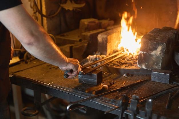 Schmied manuell auf eisen auf amboss in schmiede schmieden. behandlung von geschmolzenem metall.