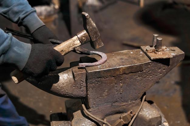 Schmied schmiedet ein hufeisen auf dem amboss mit biegedrift, nahaufnahme