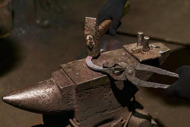 Schmied schmiedet ein hufeisen auf dem amboss mit biegegabel, nahaufnahme