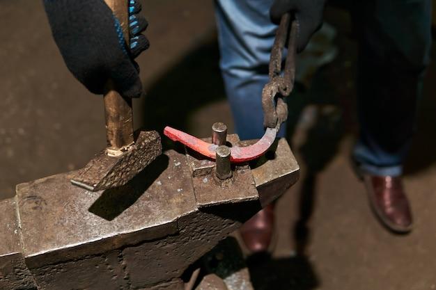 Schmied schmiedet ein hufeisen auf dem amboss mit robustem werkzeug, nahaufnahme