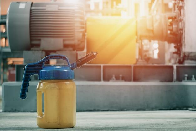 Schmiermittelflasche auf boden mit unscharfem industriellem maschinenhintergrund, ölschmierung im fabrikkonzept