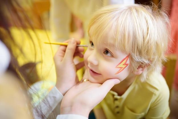 Schminken sie für netten kleinen jungen während der kinderheiterkeit mit dem gesicht.