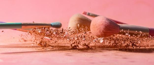Schminken sie pinsel mit pulverspritzern, die auf rosa isoliert sind