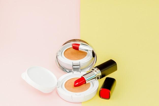 Schminken sie produkte, die auf eine leuchtend gelbe und rosa oberfläche mit kopierraum, minimalem stil verschüttet werden