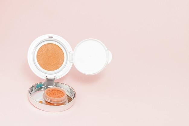 Schminken sie produkte, die auf rosafarbenem hintergrund mit kopienraum verschüttet werden, minimaler stil